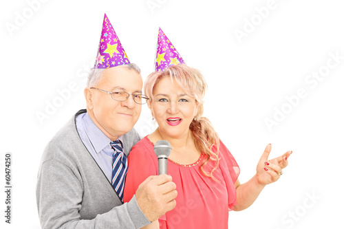 Middle aged couple with party hats singing on microphone
