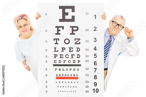 Middle aged male doctor and female patient standing behind eyesi