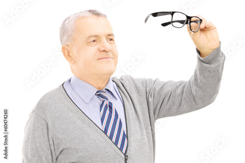 Senior gentleman holding a pair of glasses