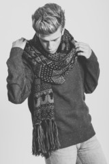 Handsome blonde man wearing sweater and scarf
