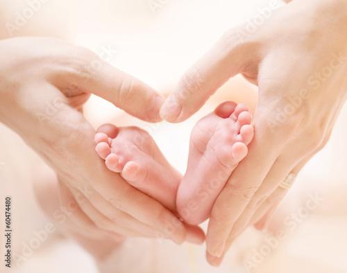 Leinwanddruck Bild Tiny Newborn Baby's feet on female Heart Shaped hands closeup