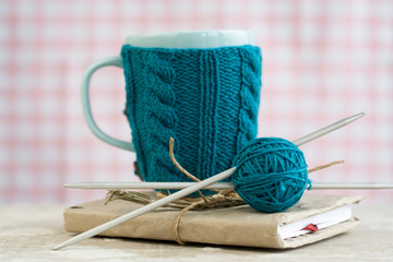 Blue cup in a blue sweater standing on an old notebook