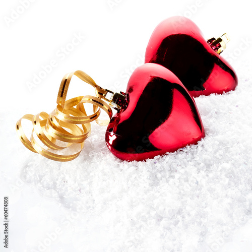 Two red hearts with gold tapes on snow