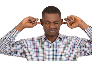 Man covering his ears, annoyed by loud noise