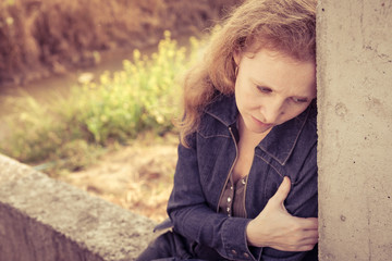one sad woman sitting  near a  wall