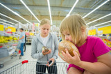 Adorable girl at shopping cart  and mother select products in su