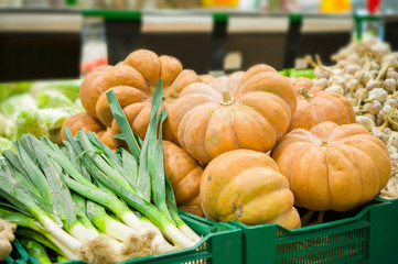 Bunch of new harvest pumpkins on boxes in supermarket
