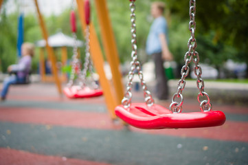 Set of red chain swings on modern kids playground