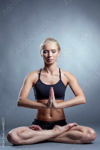 Pretty young blonde meditating in lotus position