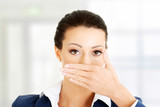 Young business woman covering her mouth