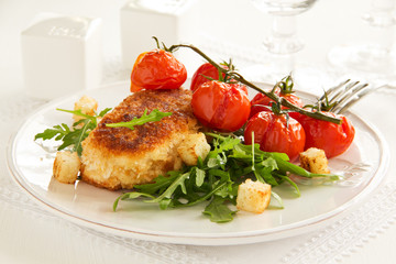 Chicken cutlet with grilled tomatoes and salad.