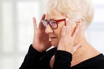 An old woman is eye glasses is having a headache.