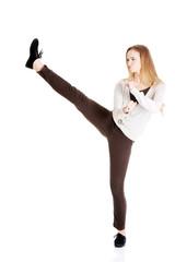 Beautiful casual woman doing a kick.