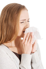 Beautiful woman sneezing, holding a tissue.