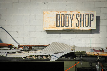 Recession Image Of Grungy Sign For A Rundown Body Shop