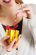 Beautiful woman unwrapping small present.