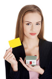Beautiful business woman holding small house and personal card.