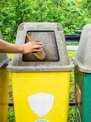hand putting a plastic glass into a recycling bin