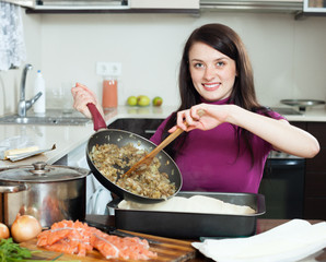 Smiling  woman cooking fish pie