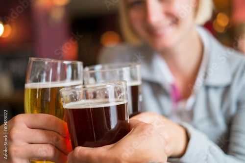 People with beer toasting in a pub