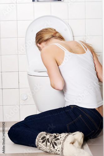 Young caucasian woman is vomiting in the bathroom.