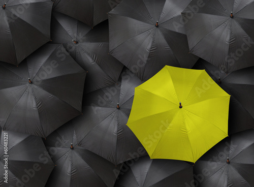concept for leadership with many blacks and yellow umbrella