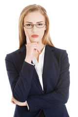 Beautiful business woman in eyeglasses with finger on her cheek.