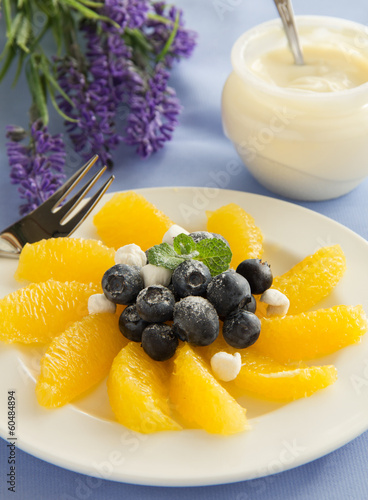 Delicious fruit salad with oranges, blueberries and cream.