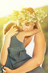 mother in a wreath in the embrace holding baby