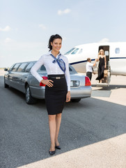 Attractive Stewardess Standing Against Limousine And Private Jet