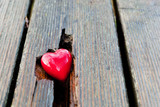 Red heart in crack of wooden plank. Symbol of love