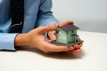 住宅の模型を使って説明しているビジネスマン