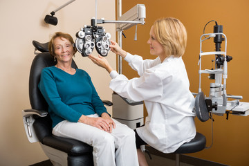 Eye Specialist Adjusting Phoropter For Woman