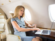 Confident Businesswoman Using Laptop In Private Jet