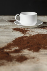 Coffee cup  and coffee powern on wooden table dark background