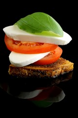mozzarella with tomatoes and basil leaf on a black background