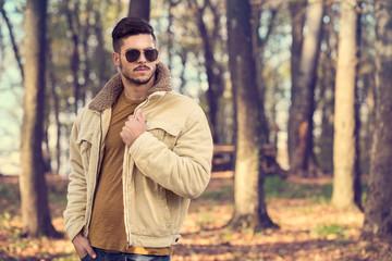 Stylish man posing in autumn park