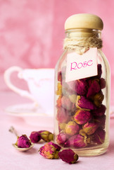 Dried rosebuds tea in a glass bottle