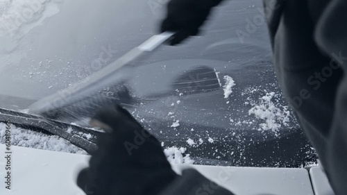 winter driving - woman sweeping snow from a windshield