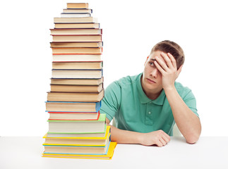 frustrated student sitting at the desk with high books stack
