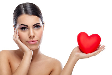 Pensive woman holding red heart