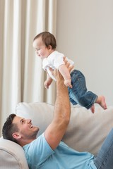 Happy father playing with cute baby