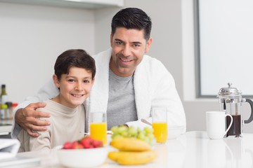 Young son with father having breakfast in kitchen