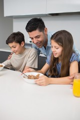 Young kids enjoying breakfast with father in kitchen