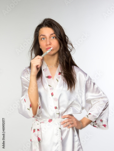 Woman in peignoir with toothbrush