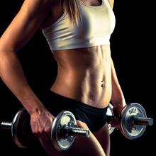 Fitness fille - jolie jeune femme travaillant avec des haltères