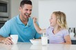 Daughter feeding cereals to father at table