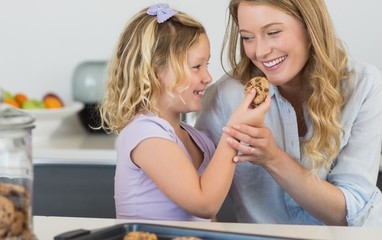 Girl feeding cookie to mother in kitchen