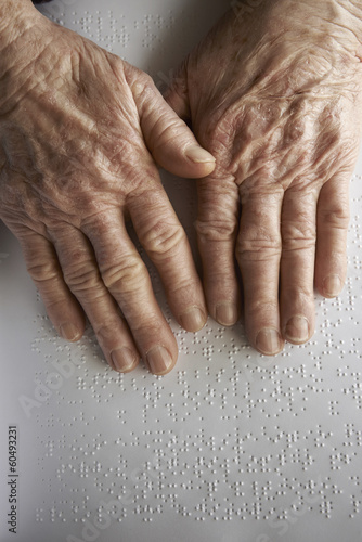 Old woman' s hands, reading a book with braille language