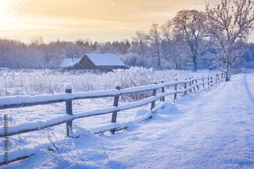 Rural house with a fence in winter